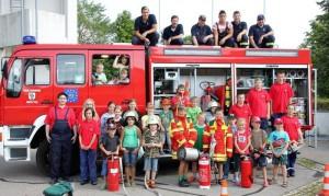Zum obligatorischen Erinnerungsfoto stellten sich die Kinder mit einigen Geräten der Feuerwehr vor dem großen Tanklöschfahrzeug auf. Foto: Ernst Häge